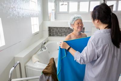 woman helping a senior woman taking a bath