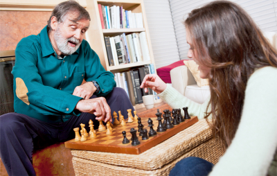 senior playing chess with a caregiver