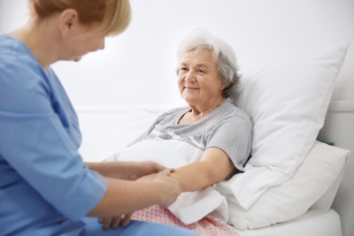 caregiver massaging the hand of senior woman at home